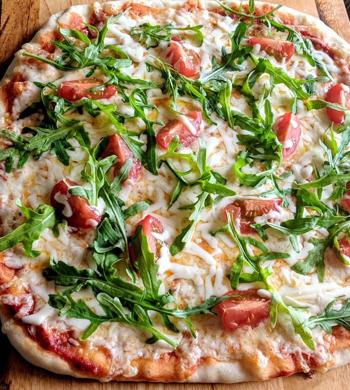 Пицца с рукколой, помидорами черри и моцареллой готова.